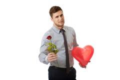 O homem novo com uma rosa vermelha e o coração balloon Foto de Stock Royalty Free