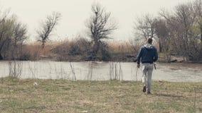 O homem novo com vara de pesca que anda na costa do rio para trás vê filme