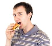 O homem novo come um Hamburger Imagens de Stock Royalty Free