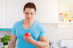O homem novo comendo saudável come o fruto da maçã no copyspac da cozinha foto de stock royalty free