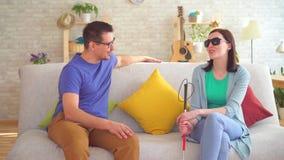 O homem novo comunica-se com uma mulher cega com uma inabilidade, sentando-se no sofá video estoque