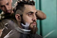 O homem novo considerável com barba senta-se em uma barbearia O barbeiro barbeia os cabelos na parte traseira foto de stock