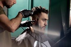 O homem novo considerável com barba senta-se em uma barbearia O barbeiro em luvas pretas barbeia os cabelos no lado imagem de stock royalty free