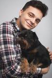 O homem novo considerável do moderno do retrato do close up, beijando seu cão preto do bom amigo isolou o fundo claro Emoções hum fotografia de stock royalty free
