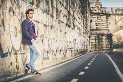 O homem novo considerável e encantador fora inclina-se contra uma parede na cidade fotografia de stock