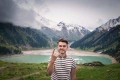 O homem novo considerável está estando no monte com vista no lago imagens de stock