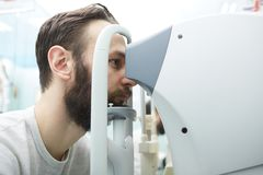 O homem novo considerável está verificando a visão do olho na clínica moderna da oftalmologia Paciente na clínica da oftalmologia imagem de stock