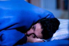 O homem novo considerável na cama com olhos abriu a desordem de sofrimento da insônia e de sono que pensa sobre seu problema imagem de stock royalty free