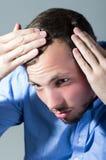 O homem novo considerável preocupou-se sobre a queda de cabelo Imagens de Stock Royalty Free
