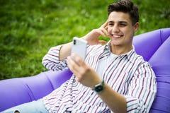 O homem novo considerável que encontra-se no lamzac inflável do sofá leu a notícia no telefone ao descansar na grama no parque fotografia de stock