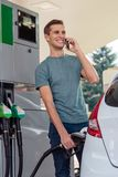 O homem novo conversa no telefone ao reabastecer o carro foto de stock