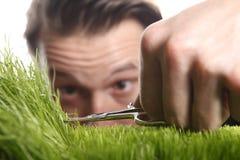 O homem novo corta o gramado inglês fotos de stock royalty free