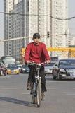 O homem novo dá um ciclo no centro do Pequim com prédios de apartamentos no bakcground, China Imagens de Stock