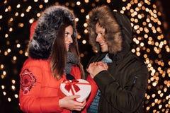 O homem novo dá um presente da mulher para o aniversário imagem de stock royalty free