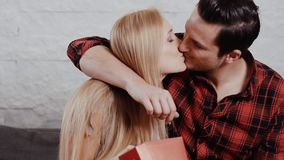 O homem novo dá um presente a uma menina no sofá vídeos de arquivo