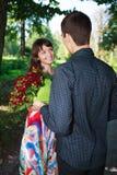 O homem novo dá a uma menina um ramalhete de rosas vermelhas em um parque do verão Imagens de Stock