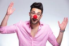 O homem novo da forma com nariz vermelho faz o gesto imagens de stock