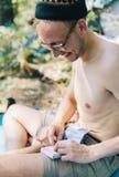 O homem novo da hippie fuma o cigarro Foto de Stock