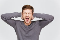 O homem novo da virada deprimida cobriu as orelhas à mão e a gritaria fotos de stock royalty free
