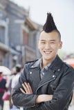 O homem novo de sorriso com Mohawk punk e braços cruzou-se, retrato imagens de stock royalty free