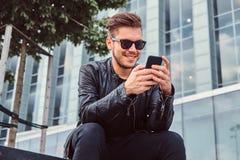 O homem novo de sorriso nos óculos de sol com cabelo à moda vestiu-se no casaco de cabedal preto usando o smartphone ao sentar-se fotografia de stock royalty free