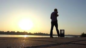O homem novo deixa cair uma bola em um banco de rio no por do sol no slo-mo vídeos de arquivo