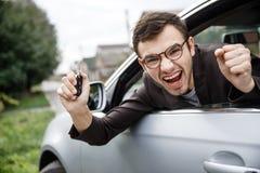 O homem novo deleitado está espreitando da janela de carro ao olhar a câmera Está guardando as chaves em seu assistente his foto de stock royalty free