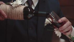 O homem novo derrama o vinho em um vidro em um restaurante, close-up, movimento lento filme