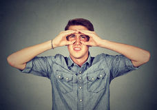 O homem novo desagradado que olha através dos dedos gosta de binóculos Fotografia de Stock