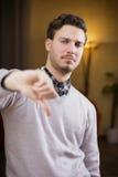 O homem novo desapontado ou desagradado que faz o polegar assina para baixo Foto de Stock Royalty Free