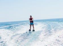 O homem novo desliza no esqui aquático nas ondas no mar, oceano Estilo de vida saudável Emoções humanas positivas, alegria A famí imagens de stock