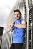 O homem novo do esporte que verifica o tempo nos crono corredores do temporizador olha guardar a garrafa de água após a sessão de Imagens de Stock