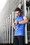 O homem novo do esporte que verifica o tempo nos crono corredores do temporizador olha guardar a garrafa de água após a sessão de Fotos de Stock
