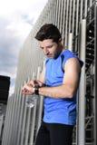 O homem novo do esporte que verifica o tempo nos crono corredores do temporizador olha guardar a garrafa de água após a sessão de Imagens de Stock Royalty Free
