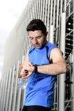 O homem novo do esporte que verifica o tempo nos crono corredores do temporizador olha guardar a garrafa de água após a sessão de Fotografia de Stock