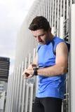 O homem novo do esporte que verifica o tempo nos crono corredores do temporizador olha guardar a garrafa de água após a sessão de Imagem de Stock