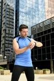 O homem novo do esporte que verifica o tempo nos crono corredores do temporizador olha guardar a garrafa de água após a sessão de Foto de Stock