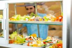 O homem novo do indicador do alimento do bar escolhe a salada Fotografia de Stock