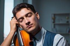 O homem novo do músico que pratica jogando o violino em casa Imagens de Stock Royalty Free