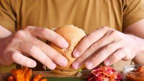 O homem novo do moderno aprecia comer e provar o hamburguer delicioso do vegetariano 4K fecham-se acima vídeos de arquivo