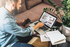 O homem novo do moderno, empresário senta-se em casa no sofá na mesa de centro, guardando o smartphone, mostrando o lápis na tela Foto de Stock