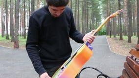 O homem novo e a guitarra na hippie denominam e o homem fuma um cigarro na floresta filme