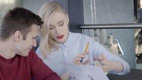 O homem novo e a mulher estão falando o assento na tabela no restaurante vídeos de arquivo