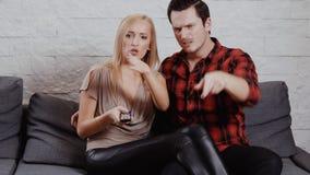 O homem novo e a mulher estão sentando-se no sofá, olhando a tevê video estoque