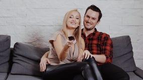 O homem novo e a mulher estão sentando-se no sofá, olhando a tevê filme