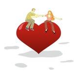 O homem novo e a mulher têm o divertimento em um coração grande Foto de Stock