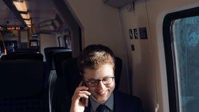 O homem novo e o homem de negócios bem sucedido que viajam pelo trem falam pelo smartphone filme
