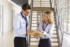 O homem novo e os doutores fêmeas discutem notas na reunião fotos de stock