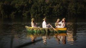 O homem novo e três meninas bonitas nas grinaldas e em camisas bordadas estão flutuando em um barco no rio slavic video estoque