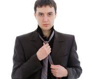 O homem novo em um terno, amarra um laço. Fotografia de Stock Royalty Free